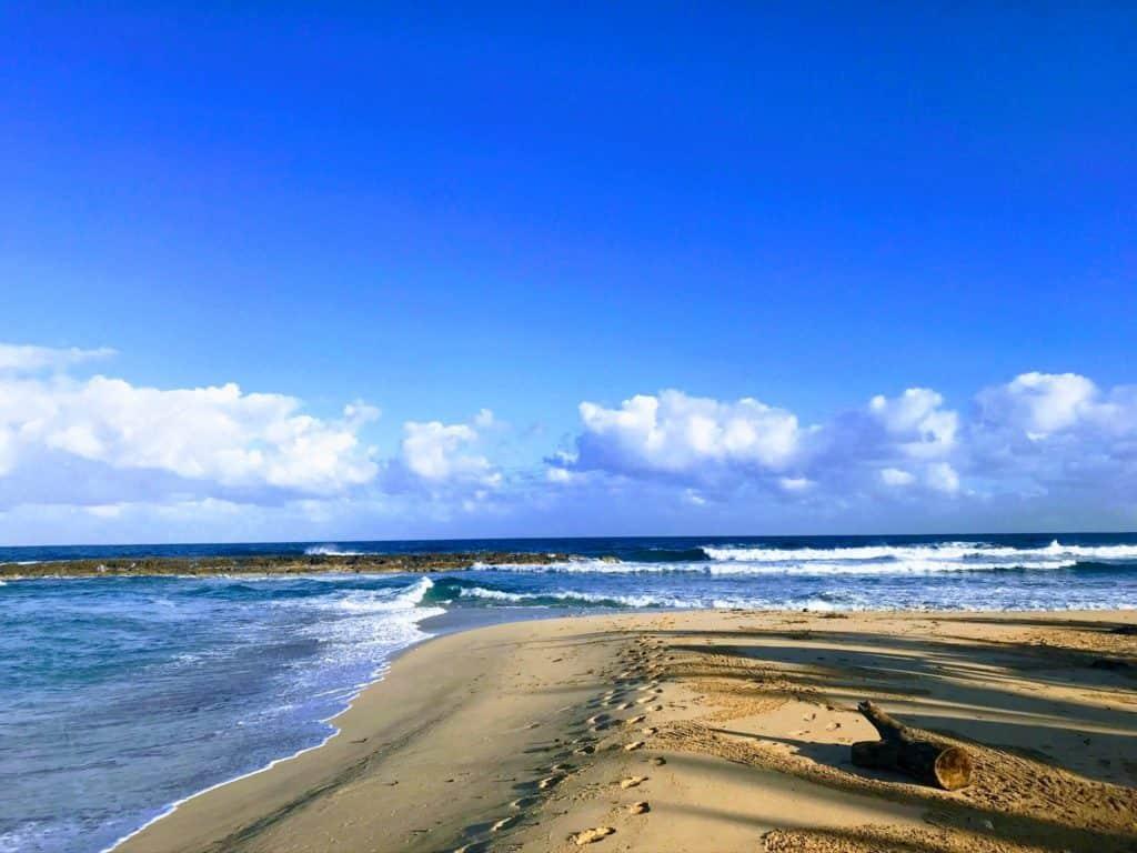Sandy beach with footsteps heading towards the ocean.