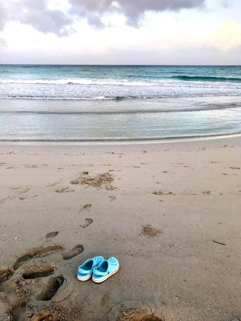 Family beach vacation packing list. Sandals on a sandy beach, with foot prints leading to the ocean.