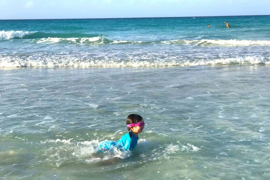 Young child wearing goggles, swimming  in the ocean. Things to pack for the beach.