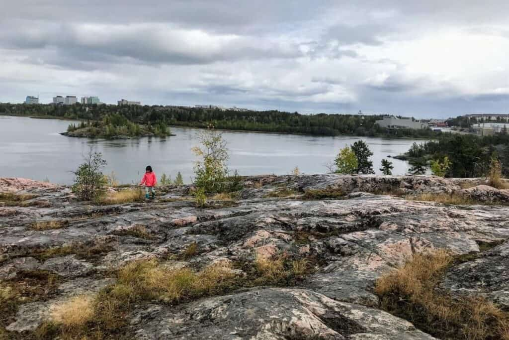 Hiking in Yellowknife - Frame Lake Trail. Young girl walking on rocks. Frame Lake and buildings in background.