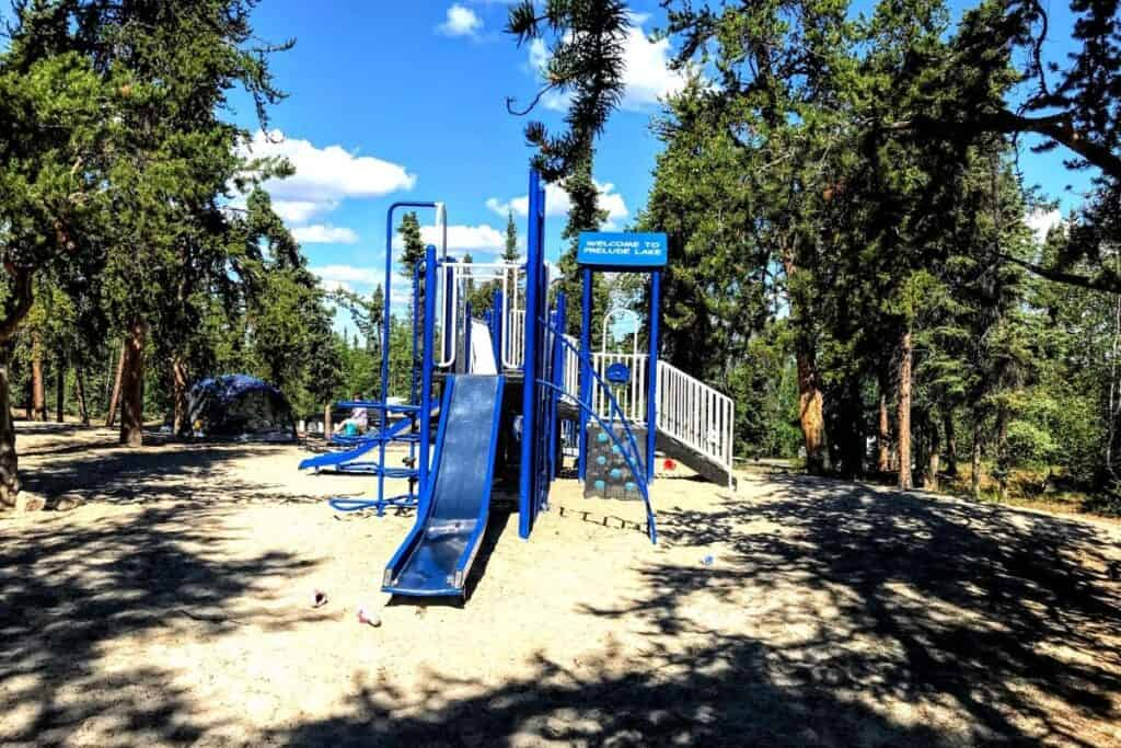 Camping, Prelude Lake, Yellowknife, NT. Kids playground, surrounded by trees.