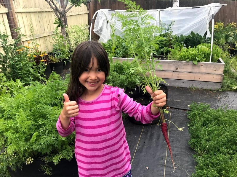 Bucket list idea, grow a garden. Young girl smiling,  holding a carrot with thumbs up.