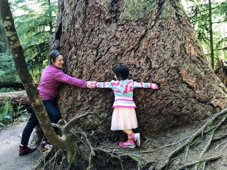 Mom and daughter wrapping arms around a huge tree trunk.