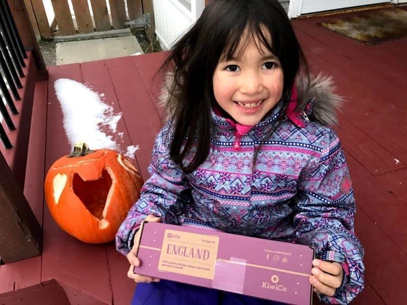 Kids camping gift. Girl smiling holding atlas craft crate.