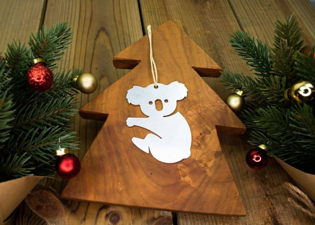 A Koala  shaped Australia Christmas ornament in metal, lying on top of a wooden tree, surrounded by tree braches with small Christmas Ball ornaments.
