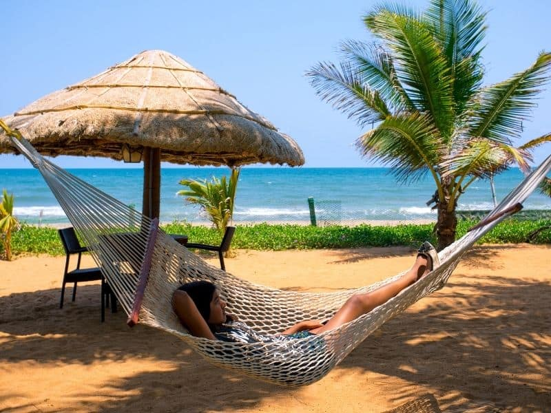 Young Girl lying in a hammock between palm trees. Tropical ocean and beach in the background.