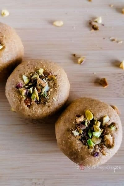 Two round Besan Ladoo cookies topped with nuts.