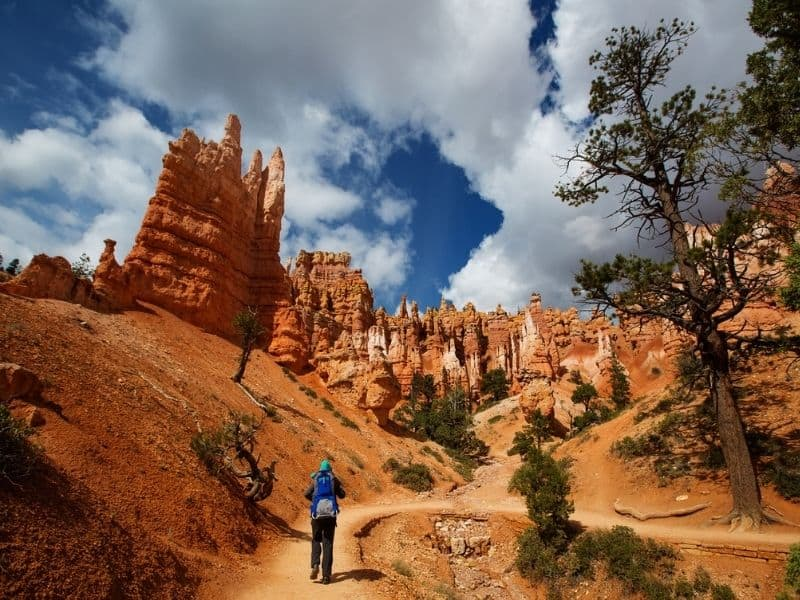 Adult carrying a child in a backpack. Hiking along trail and hoodoos in Bryce Canyon National Park.