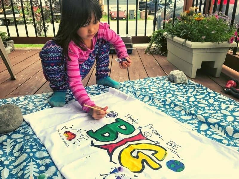 Young girl painting a pillowcase with inspirational saying. Bucket List Ideas, arts and crafts