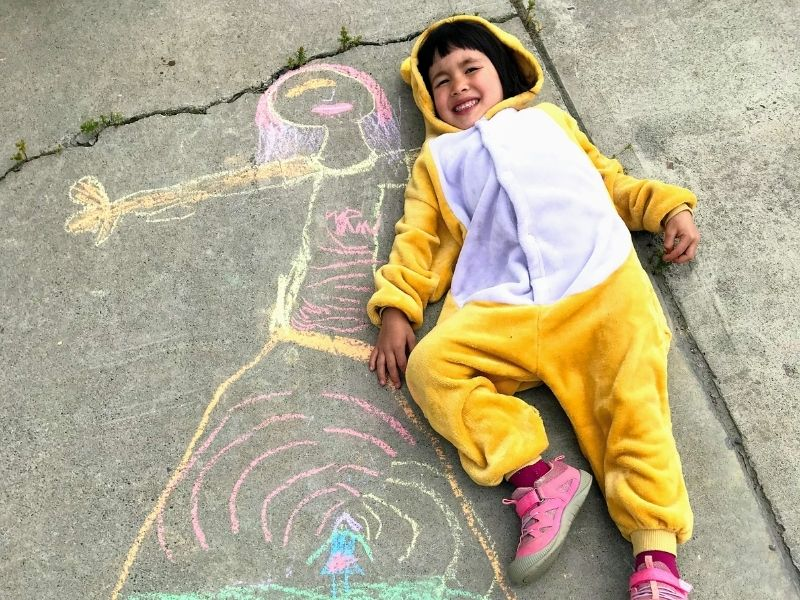 Young girl in bear costume laying beside chalk drawing of girl. Bucket list idea, chalk art
