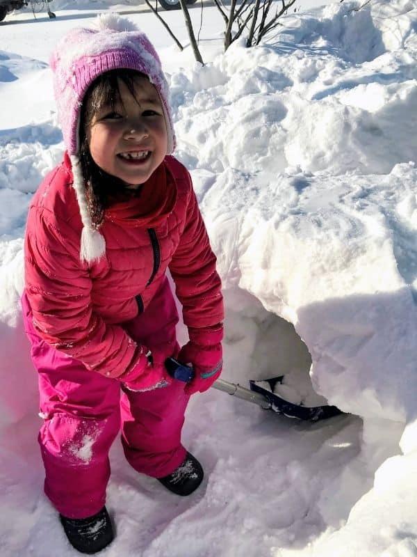 Young girl shovelling snow. Winter Bucket List Idea.
