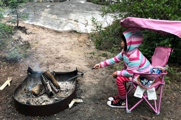 Girl roasting marshmallows over fire. Sitting in kid-sized quad chair.