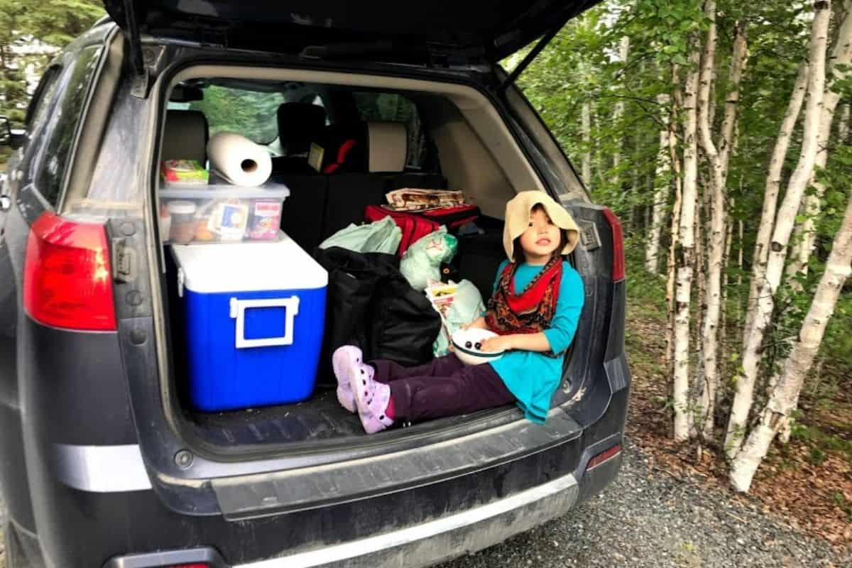 Young girl sitting in back of car full of camping gear.