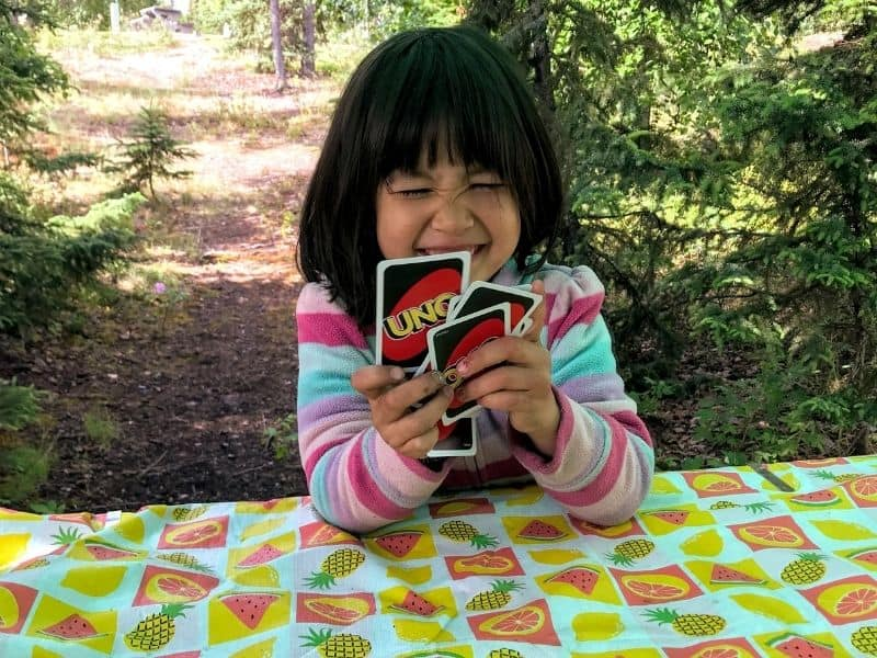 Kids Bucket List, card games. Young girl smiling holding cards outside.