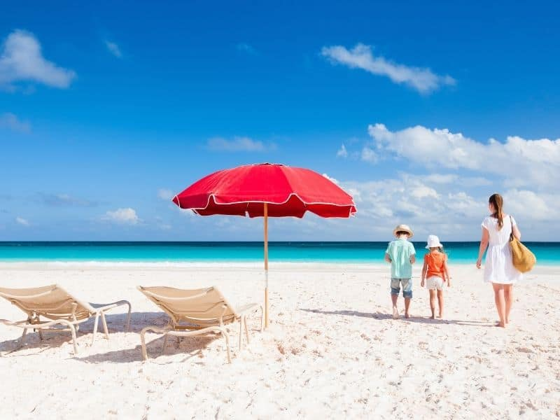 Mother, young boy and girl on beach beside two chairs and umbrella. Ocean in background.
