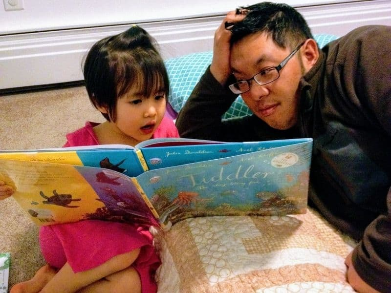 Father and daughter reading a book. Family Bucket List, reading out loud.