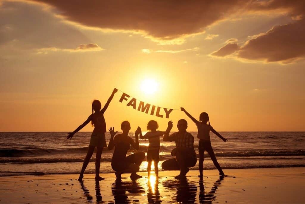 Silhouette of family of five at sunset on the beach, holding a sign that reads family.