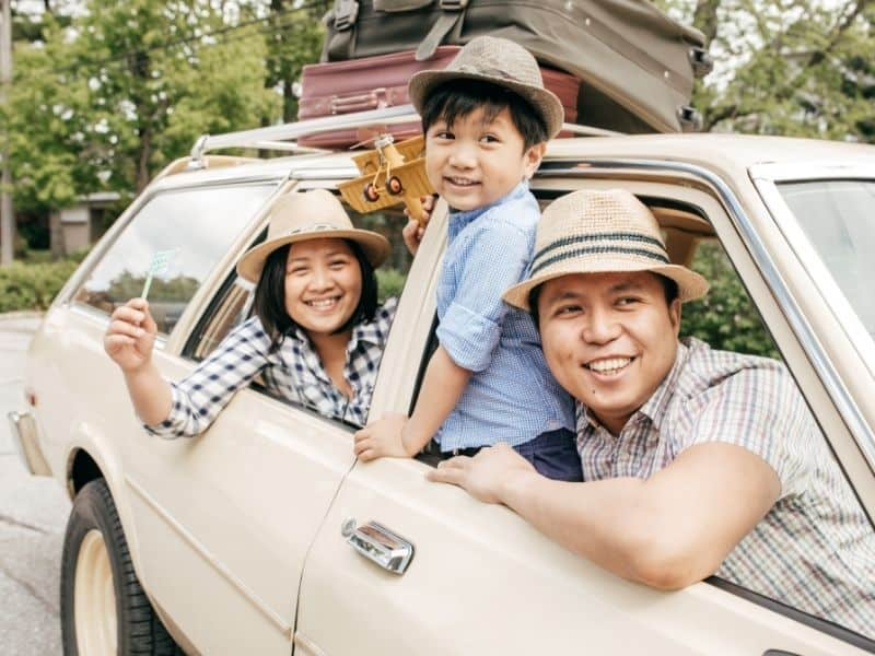 Mom, Dad, young boy of Asian ethnicity looking out side windows of car. How to stay sane on family vacation.