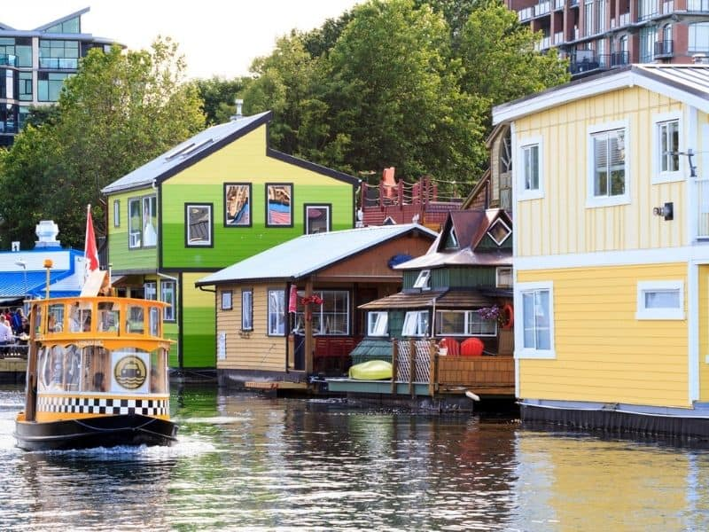 Water taxi leaving Fisherman's Wharf passing by colourful houseboats. Example of free thing to do in Victoria, BC