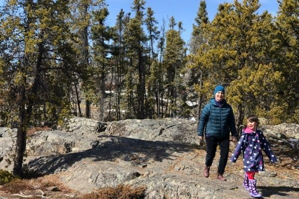 Mother and daughter hiking in pine forest.