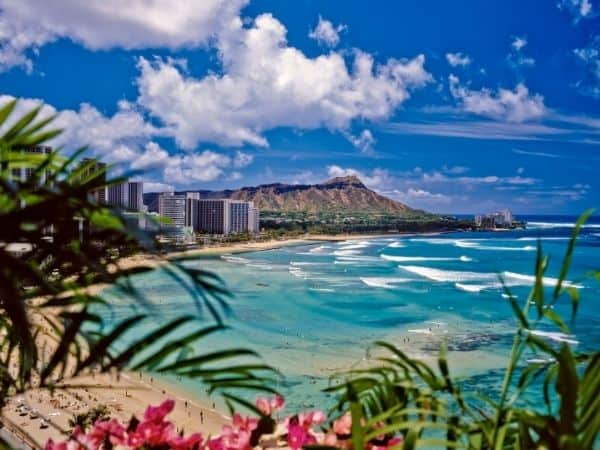 View of beach and ocean at Waikiki Beach, Honolulu. Hotels and Diamond Head in the distance.