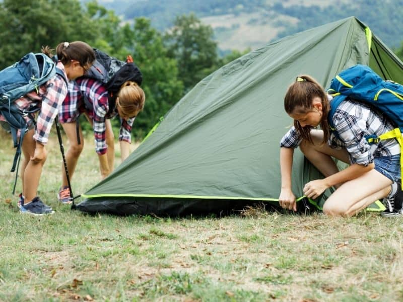 Outdoor Bucketlist Idea - camping Three young girls putting up tent