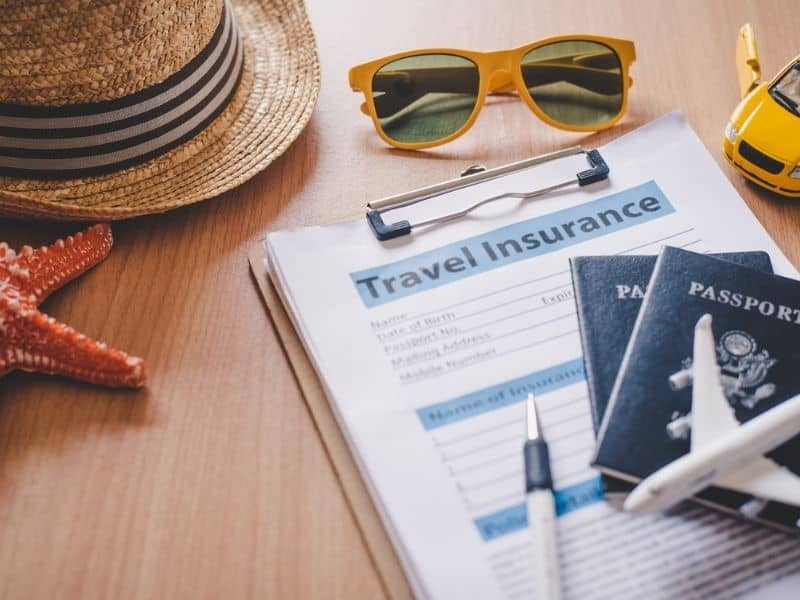 Picture of things to do before travel. Shows insurance papers with passport, and small toy plane on top. A hat, toy car, sunglasses and starfish are in the corners.