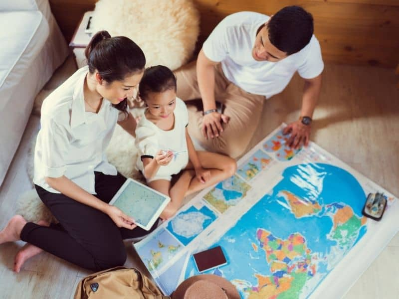 Picture of an Asian Family looking at a world map, planning a vacation.