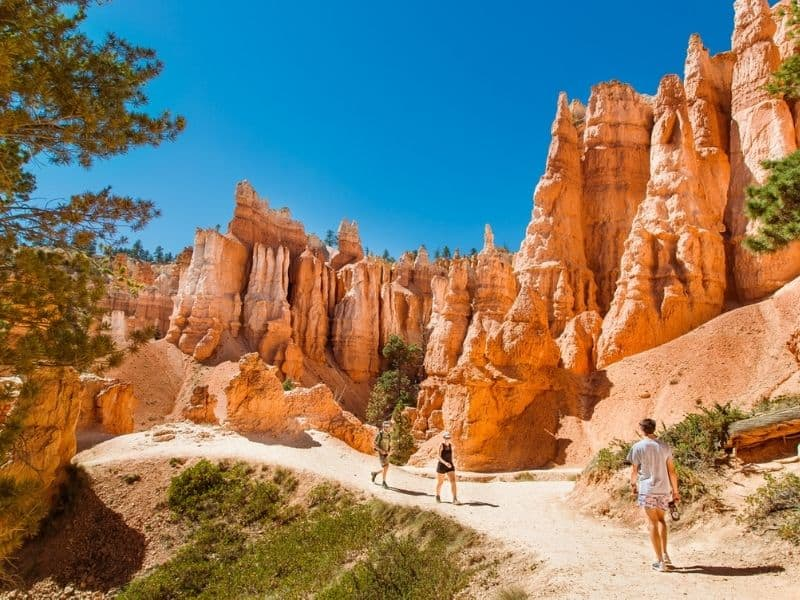 3 people hiking QUeen's Garden Trail, in Bryce Canyon, by hoodoos.