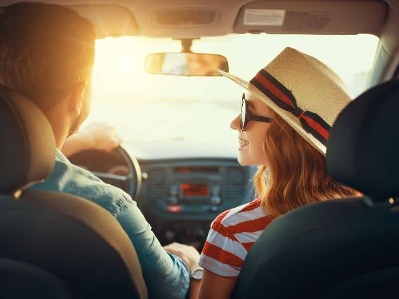 Happy couple smiling at each other in a car on road trip.