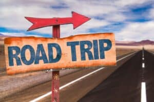 Sign on the side of the road with an arrow and text that reads road trip.
