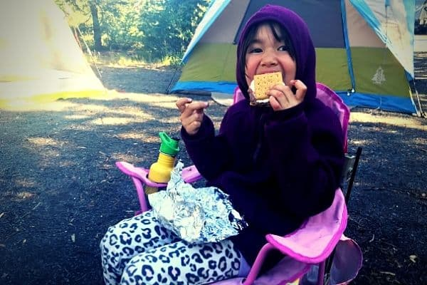 Girl eating S'Mores while camping.