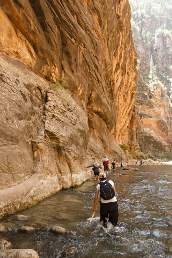 Group of people walking through the river in The Narrows, Zion National Park, UT