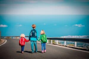 3 children walking hand in hand down road wearing travel backpacks