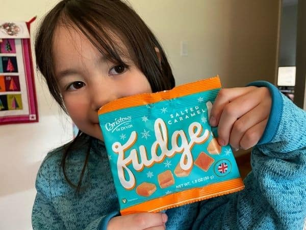 Young Girl holding a package of English Salted Caramel Fudge from Universal Yums snack box.