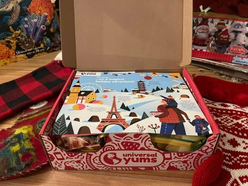 Universal Yums unboxing - box of global snacks, on floor surrounded by 3 Christmas stockings.