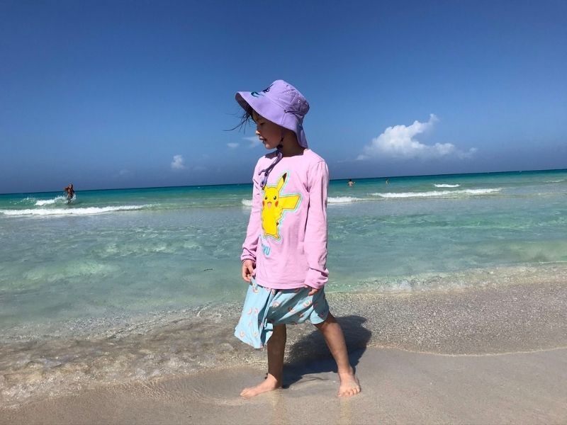 Young girl standing at the edge of a tropical ocean, on family vacation.