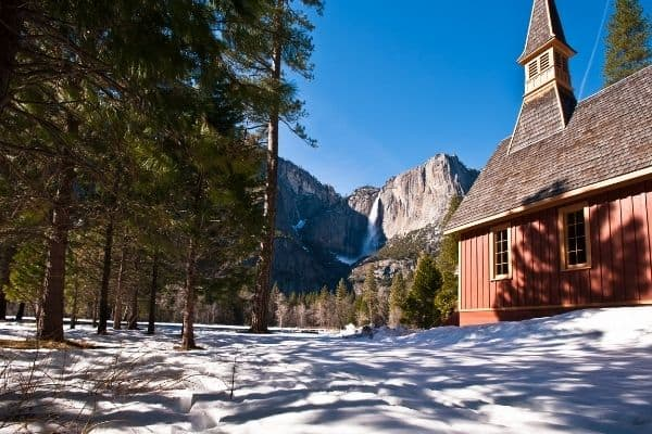 Snow on ground, in back of  a red church. Yosemite Falls, USA in background